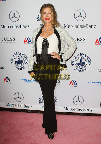 RITA WILSON .at the 32nd Annual Carousel Of Hope Ball held at The Beverly Hilton Hotel, Beverly Hills, CA, USA, .23rd October 2010..full length black  white top jacket bow ribbon clutch bag silver long maxi skirt dress hand on hip .CAP/ADM/KB.©Kevan Brooks/AdMedia/Capital Pictures.