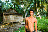 INDONESIA, Mentawai Islands, portrait of a young fisherman standing shirtless in front of fishing hut