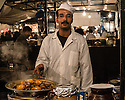 Man cooking tagine on a food stall in Djemaa el-Fna, Marrakech, Morocco.