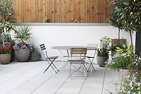 A set of outdoor dining furniture in the spacious patio area, which spans the whole of one side of the apartment