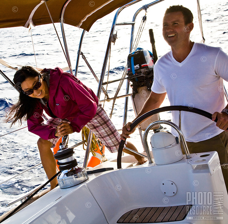 Woman trimming sail while man steers a yacht off the shores of Honolulu, Oahu, Hawaii