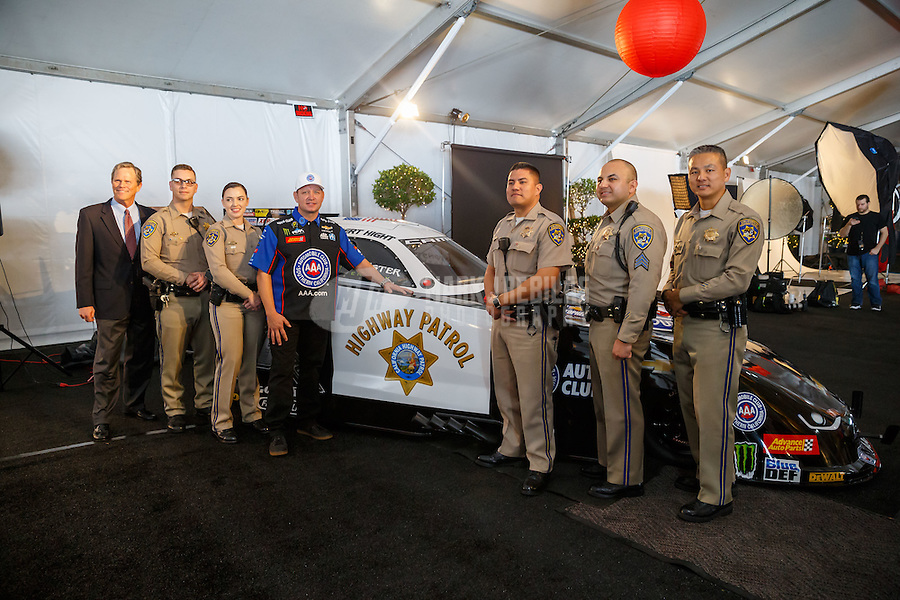 Feb 8, 2017; Pomona, CA, USA; NHRA funny car driver Robert Hight poses with officers from the California Highway Patrol alongside the CHP themed car during media day at Auto Club Raceway at Pomona. Mandatory Credit: Mark J. Rebilas-USA TODAY Sports