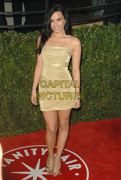 DEMI LOVATO.The 2010 Vanity Fair Oscar Party held at The Sunset Tower Hotel in West Hollywood, California, USA..March 7th, 2010.oscars full length beige gold dress strapless .CAP/RKE/DVS.©DVS/RockinExposures/Capital Pictures.