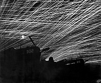 Japanese night raiders are greeted with a lacework of anti-aircraft fire by the Marine defenders of Yontan airfield, on Okinawa.  In the foreground are Marine Corsair fighter planes of the &quot;Hell's Belles' squadron.  1945.  T.Sgt. Chorlest.  (Marine Corps)<br /> Exact Date Shot Unknown<br /> NARA FILE #:  127-G-118775<br /> WAR &amp; CONFLICT BOOK #:  1235