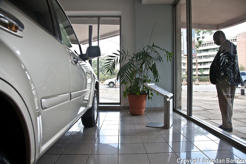 A passer-by looks at a new Nissan SUV through the display window at DT Dobie in Nairobi, Kenya.