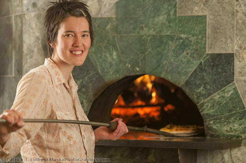 Employee uses the wood fired oven at Alaska Coffee Roasting Company, Fairbanks, Alaska
