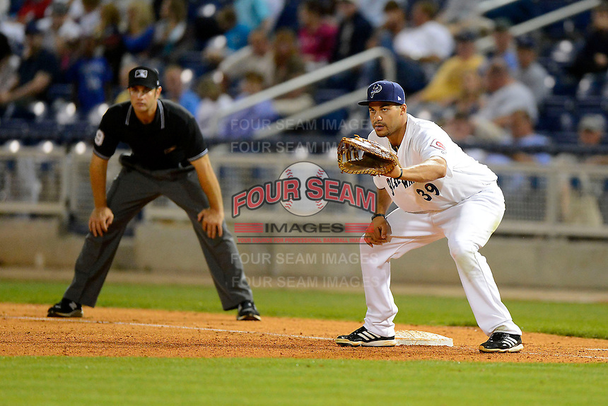 Pensacola Blue Wahoos first baseman Donald Lutz #39 holds on a runner as umpire Ryan Goodman looks on during a game against the Jacksonville Suns on April 15, 2013 at Pensacola Bayfront Stadium in Pensacola, Florida.  Jacksonville defeated Pensacola 1-0 in 11 innings.  (Mike Janes/Four Seam Images)