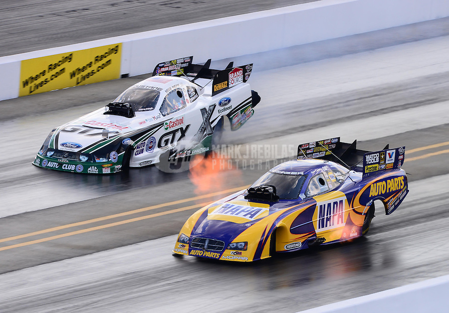 Sept. 15, 2012; Concord, NC, USA: NHRA funny car driver Ron Capps (near) races alongside Mike Neff during qualifying for the O'Reilly Auto Parts Nationals at zMax Dragway. Mandatory Credit: Mark J. Rebilas-