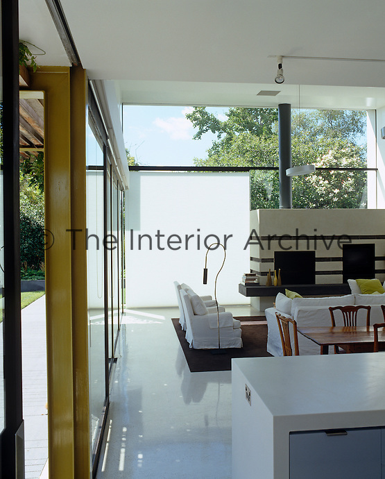 White opaque blinds against the glass walls of the open-plan living area shade the interior from the afternoon sun