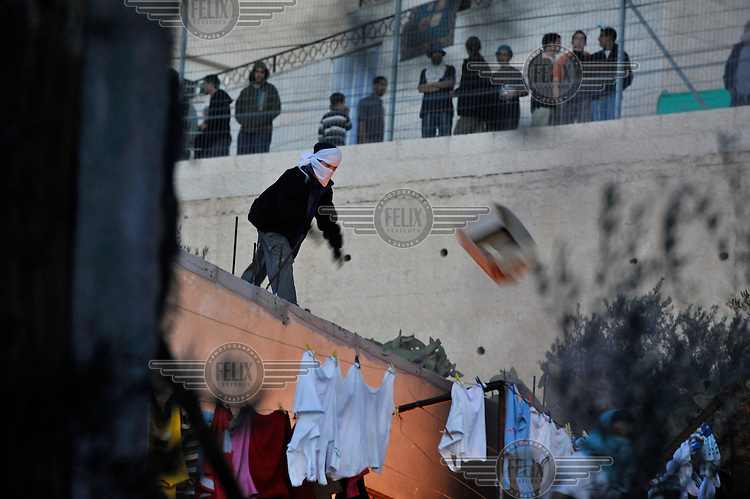 Rioting Jewish settler youths attack a Palestinian house. One throws cardboard on to a fire they had started. Violence erupted as the Israeli army evicted a group of settlers from a disputed building in Hebron. The Israeli high court had rejected the settlers' claim that they legally bought the house from its Palestinian owner. As the house became a symbol of defiance, the few families living there were joined by a mob of some 1,500 radical right-wing youths, who went on a rampage and attacked Palestinians in the mixed West Bank city.