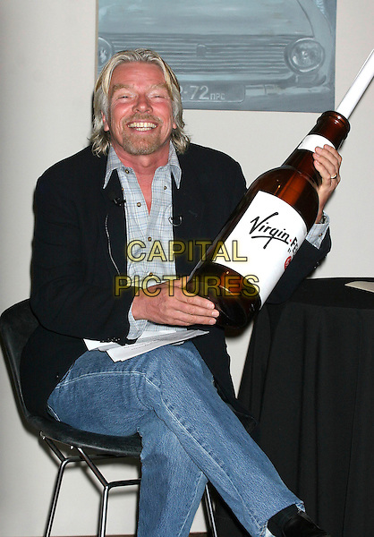 SIR RICHARD BRANSON.Announces the headliners and dates for the Virgin Festival 2007 by Virgin Moble at the Soho House, New York, New York, USA. .March 22nd, 2007.half length sitting black suit jacket bottle jeans denim.CAP/IW.©Ian Wilson/Capital Pictures