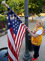 NWA Democrat-Gazette/DAVID GOTTSCHALK Sydney Bailey, Fayetteville Lions Club member, posts Monday, May 29, 2017 a U.S. flag on the square in downtown Fayetteville. Bailey was working with her husband Rick who is also a Fayetteville Lions Club member. The installation of the flags on holidays is a service project for the club and are posted through out the city including Dickson Street, the downtown square and parts of College Avenue.