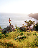 USA, California, Marin Headlands, woman hiking with the Pacific Ocean in background