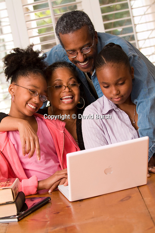 African American couple  looking at laptop with grandchildren
