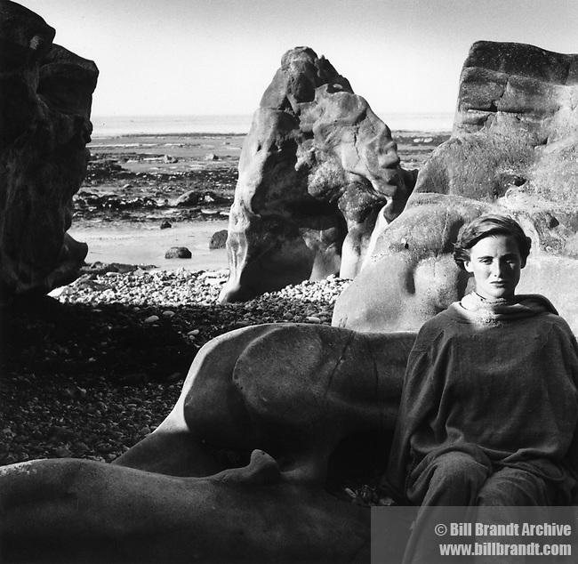 Woman sitting Etretat beach in France, 1940s