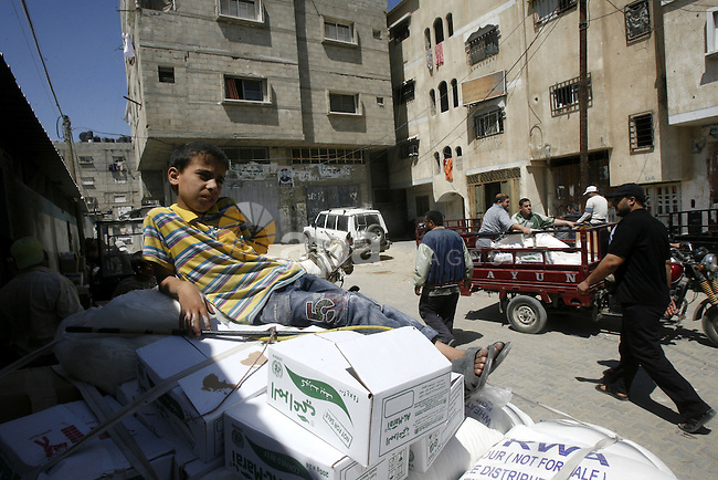 "A Palestinian boy receives monthly food aid from the United Nations Relief and Works Agency (UNRWA) center in the Rafah refugee camp, southern Gaza on May 07, 2012. The UN Agency for Palestinian Refugees (UNRWA) in Gaza launched an appeal for emergency funds to the Palestinian territories of $ 300 million (235 million), The Deputy Chief Commissioner Margo Ellis at the third anniversary of the end of the devastating Israeli operation ""Cast Lead"" in Gaza (27 December 2008-22 January 2009), said the UNRWA. Photo by Eyad Al Baba"