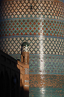 Detail of Matniyaz Divan-begi madrasah (left) 1871, with the decorative tiled brick Kalta Minor, 1855, in the background Khiva, Uzbekistan, pictured on July 6, 2010, at sunrise. Commissioned by Muhammad Niyaz the rectangular, Madrasah has  corner guldastas which are geometrically patterned in blue, white and green, with green brick domes. The Kalta Minor or Short Minaret was commissioned by Mohammed Amin Khan in 1852 to stand 70 m. high, but was abandoned when he died in 1855, and remains only 26 m. high. Khiva, ancient and remote, is the most intact Silk Road city. Ichan Kala, its old town, was the first site in Uzbekistan to become a World Heritage Site(1991). Picture by Manuel Cohen.