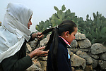 A woman help her granddaughter to prepare for school, in south Mt. Hebron, West Bank.