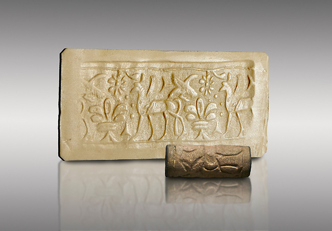 Hittite cylinder seal depicting a scene of animals, seal in foreground and impression standing behind.. Adana Archaeology Museum, Turkey. Against a grey background