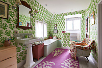 The traditional family bathroom is a riot of bold colour and pattern. The coral motif wallpaper is by Molly Mahon.
