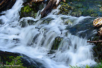 The water spread across a shallow stream before tumbling over a series of rocks.  Water droplets bounced off rocks as they continued downstream.  The softness was mesmerizing and the sound soothing.