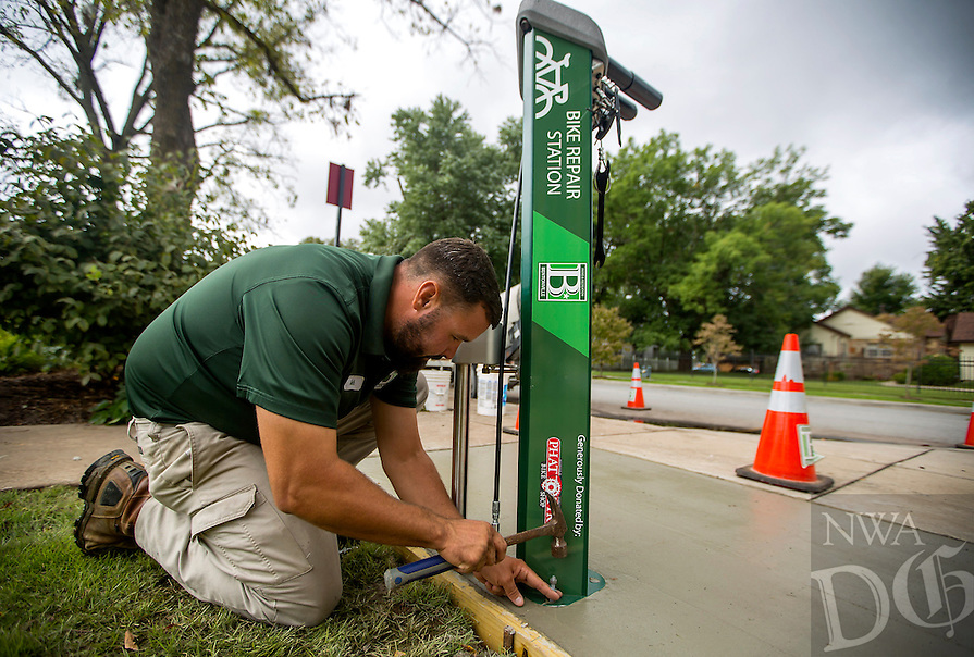NWA Democrat-Gazette/JASON IVESTER <br /> Seth Culbertson (cq) with Bentonville Parks &amp; Recreation sets the bolts on Friday, Sept. 11, 2015, for a bike repair station at the intersection of NE 3rd Street and NE A Street. The crew is installing six of the stations in the city which have attached neccessary tools and an air pump for cyclists along the Razorback Regional Greenway Trail.