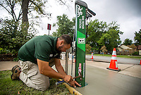 NWA Democrat-Gazette/JASON IVESTER <br /> Seth Culbertson (cq) with Bentonville Parks & Recreation sets the bolts on Friday, Sept. 11, 2015, for a bike repair station at the intersection of NE 3rd Street and NE A Street. The crew is installing six of the stations in the city which have attached neccessary tools and an air pump for cyclists along the Razorback Regional Greenway Trail.