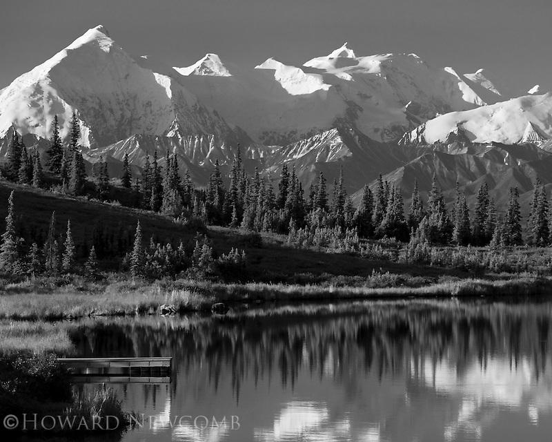 The Alaska Range and lake shore reflect in Wonder Lake on a clear and calm summer morning in Denali National Park, Alaska.