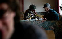 Friends share stories at a restaurant while waiting for a funeral in the central area of La Valle, Italry.