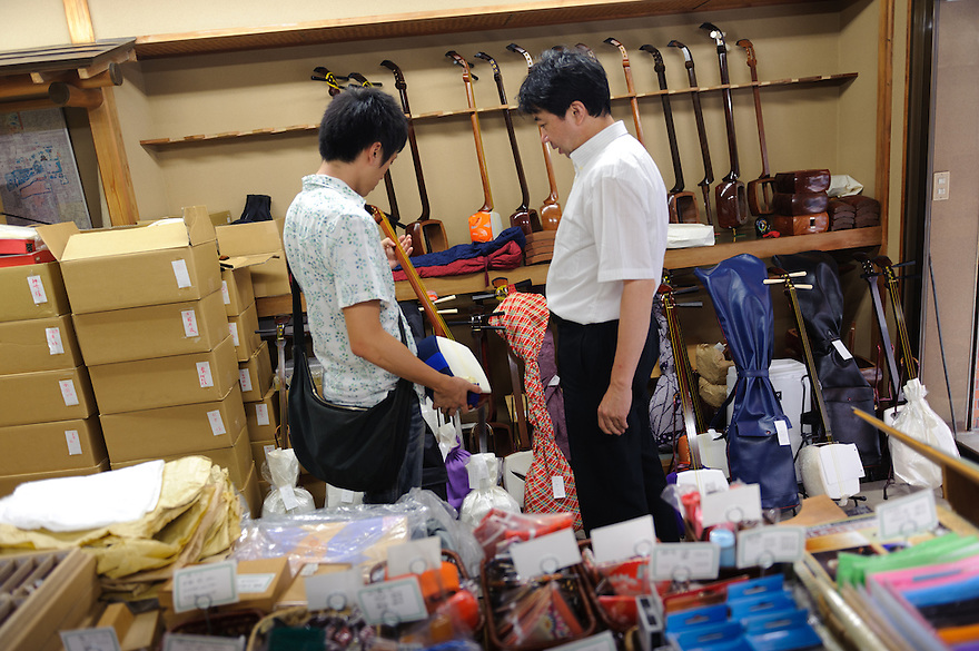 Shamisen shop owner, Kazuhiro Yoshizawa talks to a customer, Asakusa, Tokyo, Japan, August 28, 2011. Sensoji is one of the oldest temples in Tokyo, and the shopping arcades around it have sold visitors souvenirs for centuries.