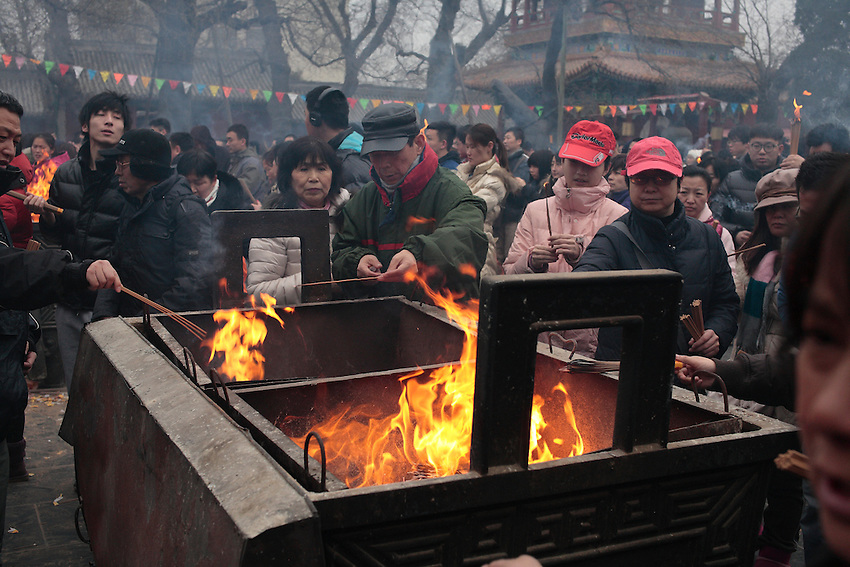 Chinese New Year( Spring festival) 2014. The crowd is packing the Lamas Temple (Yonghegong) in Beijing to offer incense and prayers the firtst day of the Lunar Year of the Horse, in order to gain luck and prosperity ,January 31 2014.