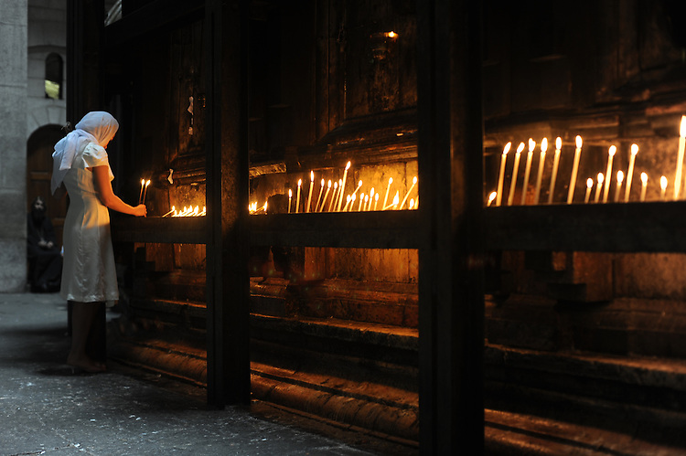A woman lights candles as she visits the Church of the Holy Sepulchre, in Jerusalem's old city.