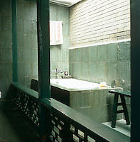 This bathroom is in a converted passage between two yards and is decorated with varnished green slate
