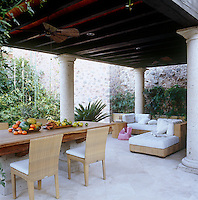 The table on the dining room terrace is custom made and is surrounded by Panama chairs, while the comfortable sea-grass chaise longues are upholstered in muslin