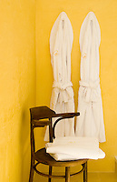 A matching pair of white towelling bath robes hangs on a bright yellow wall