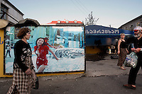 People walk past an advertising billboard in Batumi......