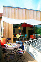 An awning is streched across the terrace where a garden table and chairs are arranged on the wooden decking