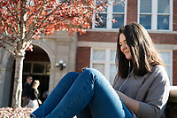 Student sitting in front of McCain Hall with fall leaves.<br />  (photo by Megan Bean / &copy; Mississippi State University)