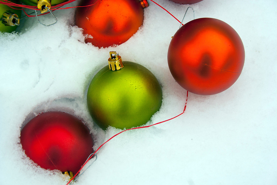 Red green and orange Christmas ornaments with raffia in fresh snowfall