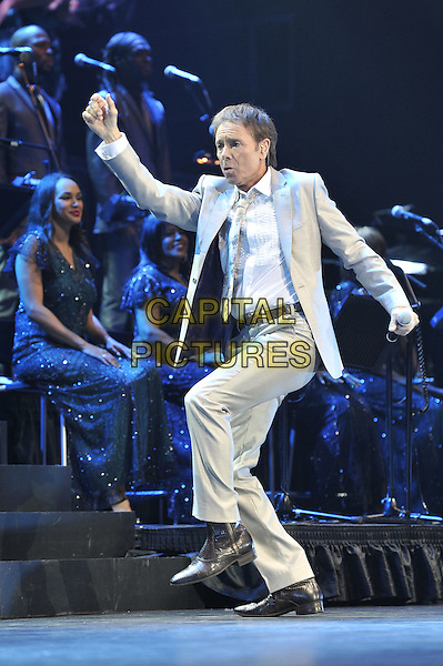 Cliff Richard.Performing live in concert at the O2 Arena, Greenwich, London, England. 25th October 2011.stage gig performance music on full length beige grey gray suit jacket white shirt arms dancing funny.CAP/MAR.© Martin Harris/Capital Pictures.