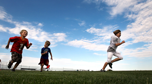 Keenan, left, Ethan and Brayden Jacobs race one another while waiting for the end of their brother Justin's football practice in Ankeny.   Their mother, Heather, lost her husband, Eric, in a plane crash in 2006 when she was eight months pregnant with their youngest, Ella, and has since been raising her five young children on her own.