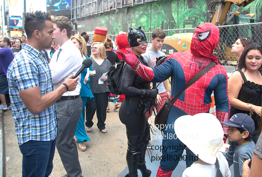 pic shows: Times Square scene of punch up between Spiderman character and policeman.<br /> TV reporters including Fox News' &quot;Kennedy&quot;  female report tries to interview Batman Spiderman and Catwoman but they angrily push her away in heated scenes.<br /> <br /> <br /> 28.7.14<br /> <br /> Pic by Gavin Rodgers/Pixel 8000 Ltd