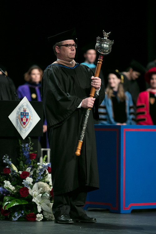 Jason Beck, assistant dean, carries the university mace during the procession Saturday, June 10, 2017, during the DePaul University School of Music and The Theatre School commencement ceremony at the Rosemont Theatre in Rosemont, IL. (DePaul University/Jeff Carrion)
