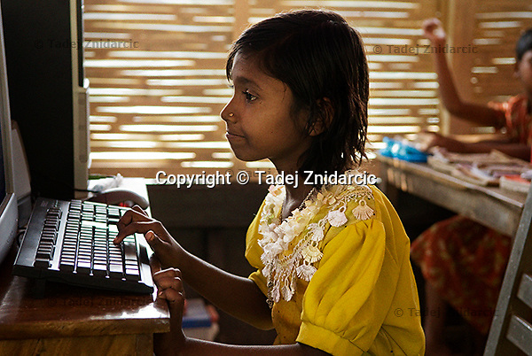 Student writes her name on a computer during a computer session on a boat school that operates on the Atrai river. Each boat school is equipped with a computer and the children can learn basic computer skills. (Photo by Tadej Znidarcic)