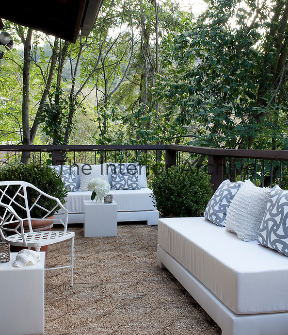 Patterned and plain cushions in grey and white fabric sit on sofas on the roof garden terrace.