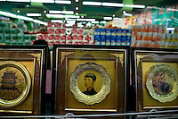 Souvenirs with pictures of a young Chairman Mao and other political images stand for sale on a shelf in a hypermarket in Nanchang, Jiangxi Province, China.