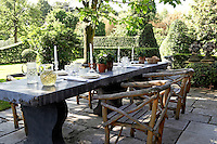 In the garden of the 19th century farmhouse a rough-hewn stone table is laid for lunch