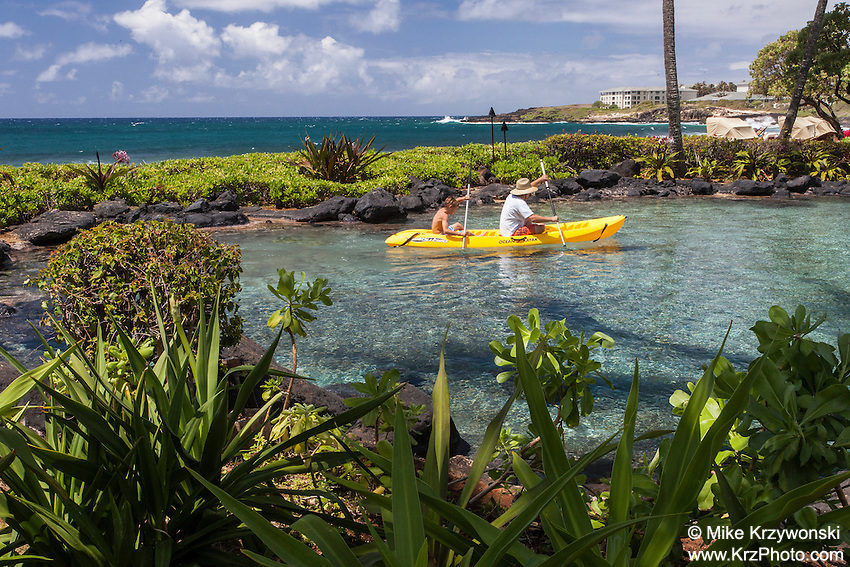 Caucasian man & boy kayaking in lagoon at at Grand Hyatt Kauai Resort in Koloa, Kauai