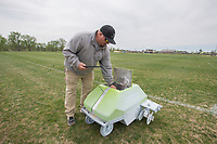 """NWA Democrat-Gazette/J.T. WAMPLER Chris Gibson, sports turf manager for the Springdale Parks and Recreation department, paints lines Thursday April 11, 201 on soccer fields at CL """"Charlie"""" and Willie George Park with the help of a line-painting robot. The Turf Tank can paint fifteen soccer fields in six hours, a task that would otherwise take three parks workers two days to do it by hand."""