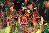 Rio de Janeiro, Brazil. Samba school; four girls dressed as indians in red and green feathers; Carnival.
